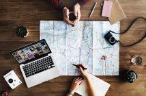 personnes organisant un voyage avec carte ordinateur appareil photo