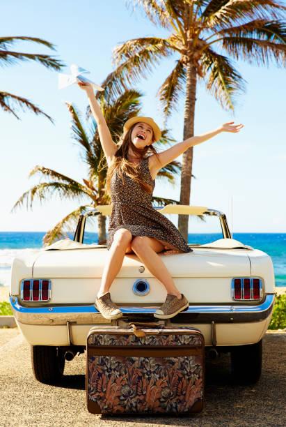Jeune femme heureuse assise sur la capot de sa voiture devant la plage
